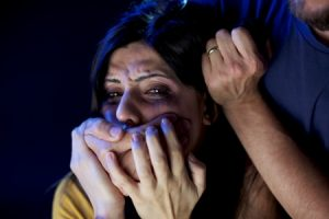 15252303 - strong man holding face of beautiful desperate woman crying