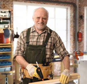 31621788 - senior happy casual caucasian handyman working at diy workshop with tools, belt, wearing gloves. smiling.